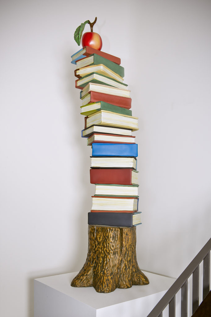 Books stacked on top of a tree stump with an apple on the top