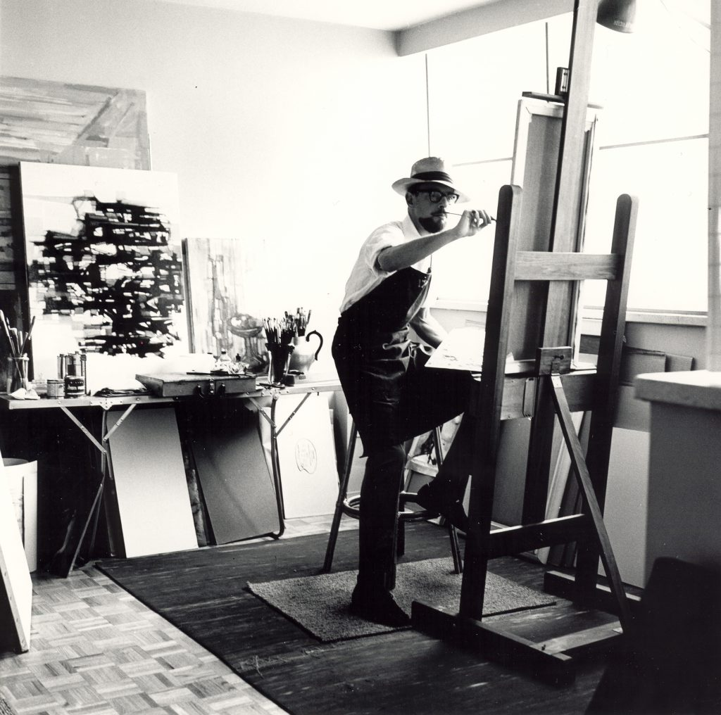 Artist in studio painting at an easel