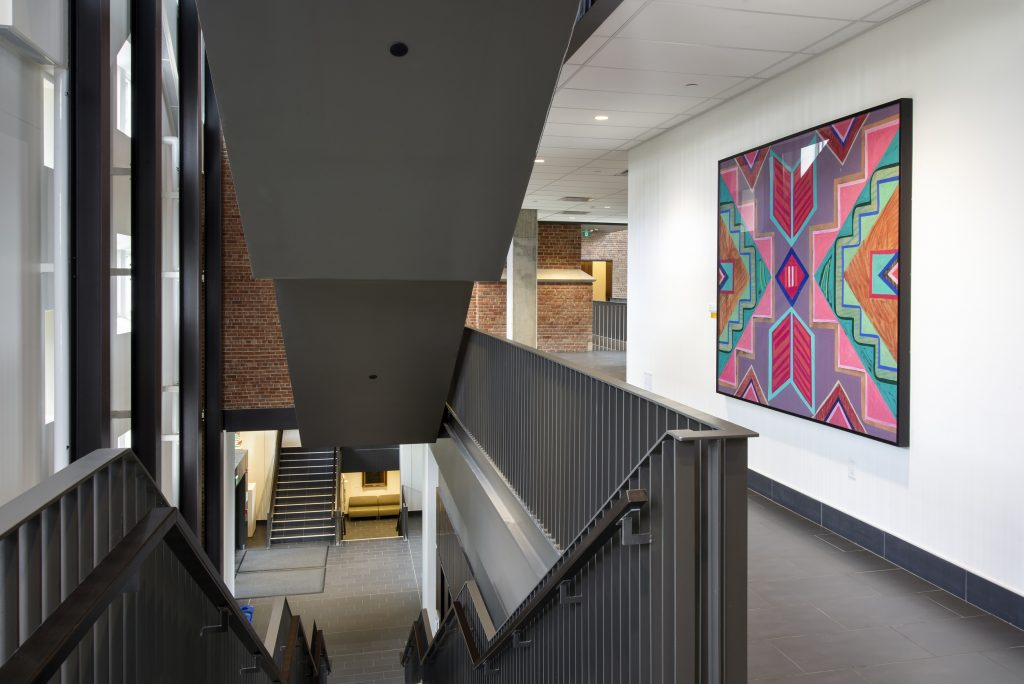 View of a brightly-patterned abstract painting in a hallway, next to a stairwell