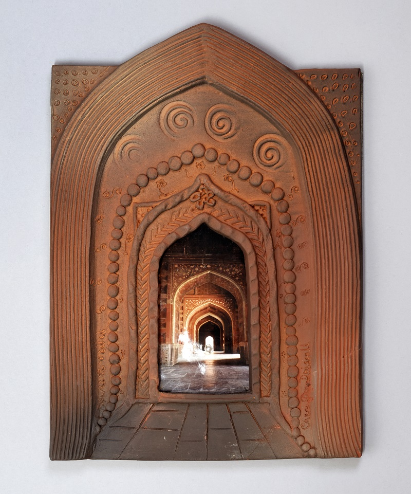 Image of a flat terracotta sculpture of arches surrounding a photograph of arches. At the centre is a tiny pearl bead.