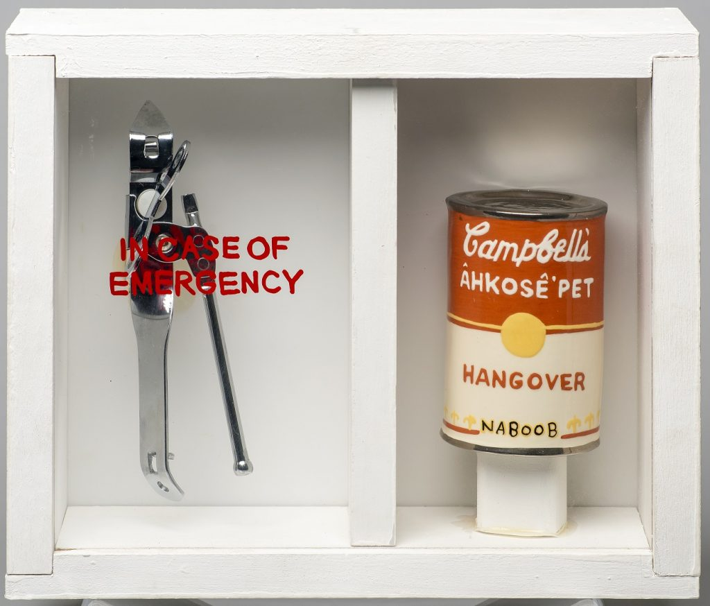 """Image of a sculpture of a white, wooden box with a plexiglass front. On the left side is a silver can opener, underneath the words """"In case of emergency"""" written on the glass. On the right side is a ceramic sculpture of a Campbell's soup can, with the words """"CAMPBELL'S ÂHKOSÊ'PET / HANGOVER / NABOOB"""""""