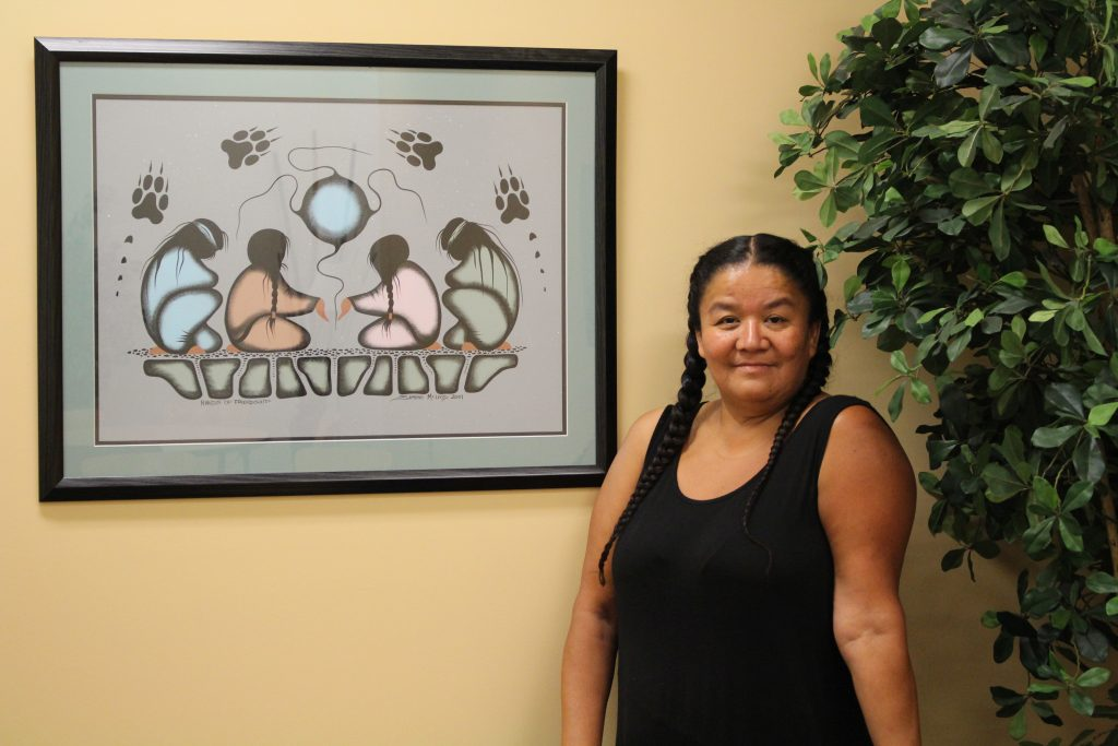 """Artist Simone McLeod with her artwork """"Hands of Friendship"""" in our Faculty Lounge. Photo Credit: Shuana Niessen"""